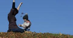 Little baby and young mother play with autumn leaves, blue serene sky, 4K Stock Footage