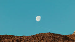 Desert Mountain Moon Rise with Contrail - stock footage
