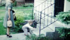Vintage 1950s Child Running on front lawn Stock Footage