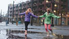 Two Friends Enjoy The Rain, Dance And Twirl In Big Puddle - stock footage