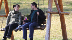 Young family have fun in nature, all laugh and enjoy to balance in the swing - stock footage
