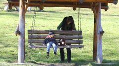 Young mother push the wooden swing with little boy and teddy bear Stock Footage