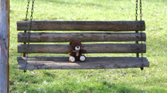 Single  teddy bear sitting on wooden swing, balancing in nature - stock footage