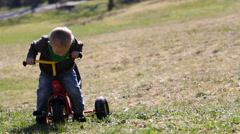 Adorable baby on colored tricycle pick a flower, smell it, put it down on meadow Stock Footage