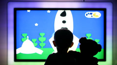 Little baby and teddy bear silhouette watching TV cartoons motion  on big screen Stock Footage