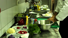 chef in the action in kitchen  making  vegetables salad - stock footage