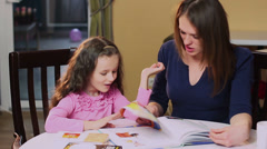 Happy mother teaches little daughter color book, learning colors - stock footage