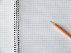 pencil on copy-book - stock photo