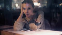 Sad beautiful woman with a glass of wine looking through the bar window Stock Footage