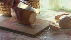 Slicing fresh, crusty bread on chopping board super slow motion, shot at 240fps Stock Footage