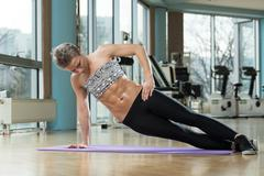 smiling woman doing abdominal excerise - stock photo
