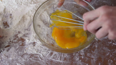 Beating eggs with whisk in glass bowl, on a table full of flour Stock Footage