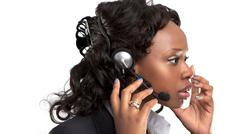 Smiling businesswoman talking on a customer service telephone headset. Stock Photos