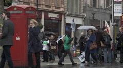 Peaceful protestors pass a phonebox Stock Footage