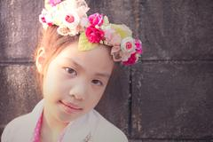 lovely little girl with flowers on the head - stock photo