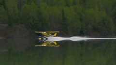 Alaskan Floatplane Accellerating to Take off from Calm Mountain Lake Stock Footage