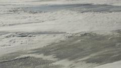 Blowing Snow over Crusty River Ice Med Pan Stock Footage