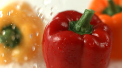 Water splashing on bell peppers, slow motion Stock Footage