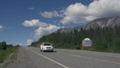 Cars Heading both Directions into and out of Canada Past Mountainous Stock Footage