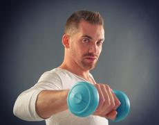 handsome man holding dumb bells - stock photo