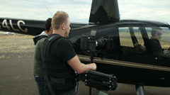 Behind the scenes, shooting a businessman getting out of a helicopter - stock footage