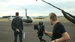 Behind the scenes, crew shoots helicopter talking off - stock footage