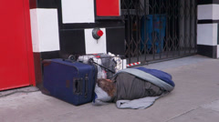 Down and Out Homeless Man Sleeping on Sidewalk with Luggage Stock Footage
