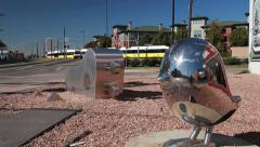 Dallas Dart Train passes by small sculpture sunny day B-Roll Stock Footage