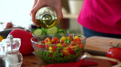 Pouring olive oil on fresh salad in bowl, super slow motion, shot at 240fps Stock Footage