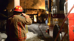 Firefighter Operating pump with fire and flames in background Stock Footage