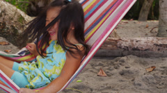 Young girl playing in hammock at beach, Costa Rica Stock Footage