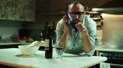 Young man with cellphone drinking red wine in his kitchen - stock footage