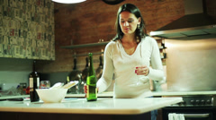 Young woman testing owful wine in her kitchen Stock Footage