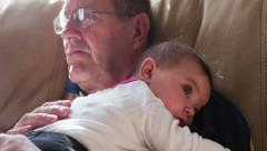 Grandpa holding child on lap while watching TV tilt 4k Stock Footage