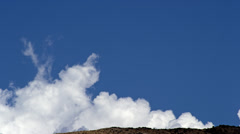 Cumulus Clouds grow over hillside 4K Stock Footage