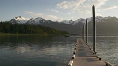 Outboard Fishing Boat Passing Alaskan Dock in Evening wtih Mountains Stock Footage