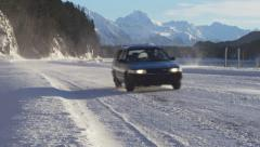 Passing Car and SUV on Snowy Road Alaska Sunny Inlet Mountains Backg Stock Footage