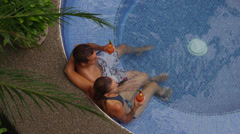 Couple sitting in hot tub together enjoying a drink - stock footage