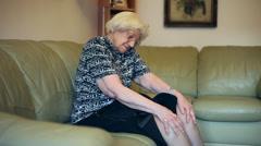 Elderly woman suffering after knee surgery, trauma, grandma having pain, massage Stock Footage