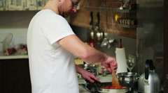 Young man preparing and tasting dinner in his kitchen Stock Footage