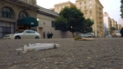 Slum Trash in SF City Street - Discarded Syringe low angle with Traf Stock Footage