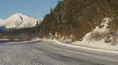 Spindrift Slithering on Empty Sunny Snowy Road in Alaska Winter Drive Stock Footage