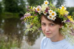 Girl  in camomile chaplet Stock Photos