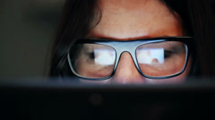 Closeup shot of woman in glasses surfing internet at night - stock footage