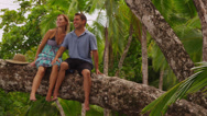 Stock Video Footage of Couple sitting together on tree at beach, Costa Rica