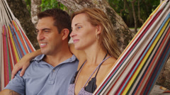 Couple sitting together in hammock at beach, Costa Rica Stock Footage