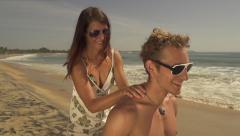 Girlfriend greasing her boyfriend with suntan lotion - stock footage