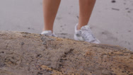 Stock Video Footage of Closeup of woman tying running shoe at beach