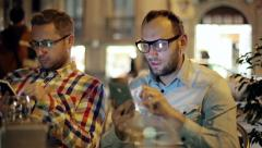 Two guys with smartphones in the restaurant at night Stock Footage