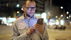 Young man with smartphone in night city, steadicam shot Stock Footage